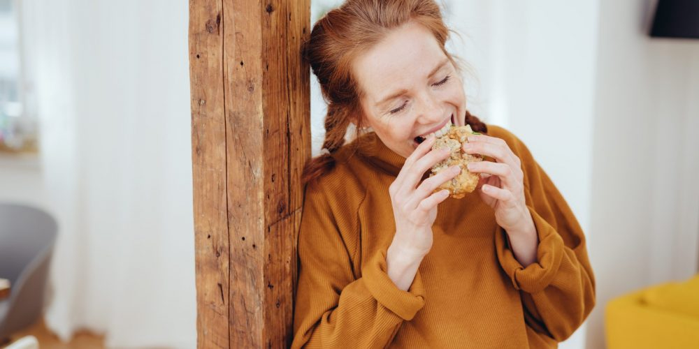 Hungry young woman taking a bite of a healthy wholewheat sandwich with a happy smile leaning on a wooden pillar indoors at home